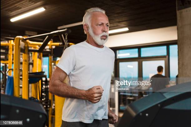 senior man using treadmill gym morning