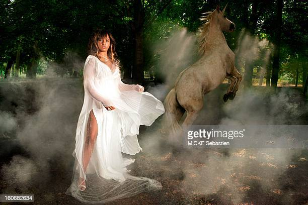 Feerique appearance of Chimene BADI dressed in a white lace dress from Calais near a horse turns into unicorn magically in the morning mist the Bois...