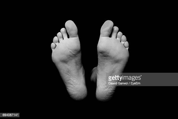 feet against black background - leiche stock-fotos und bilder