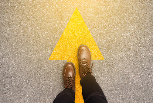 Feet and arrows on road background in starting line beginning idea. Top view. Woman in leather ankle boots on pathway with yellow direction arrow symbol. Moving forward, new start and success concept. 1186015952