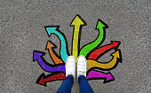 Feet and arrows on road background. Pair of foot standing on tarmac road with colorful graffiti arrow sign choices
