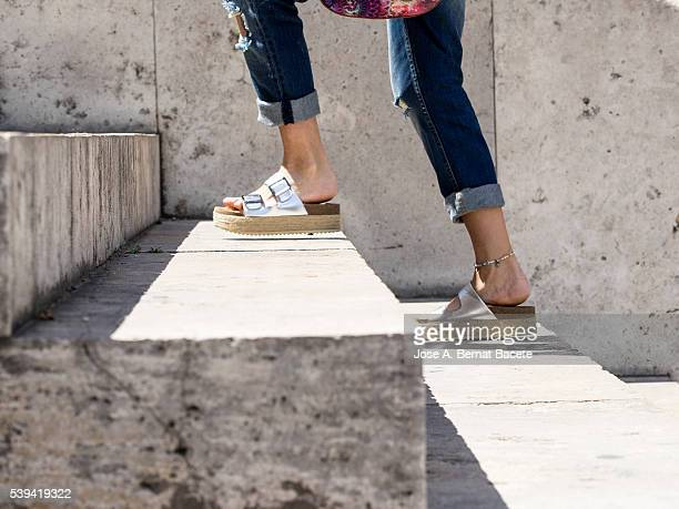 Feet and legs of a young woman with summer footwear raising a few stairs outdoors