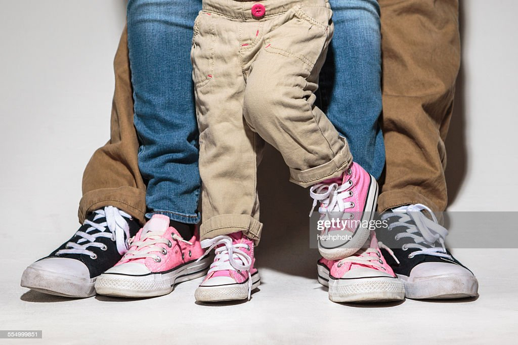 Feet and legs of family with toddler daughter : Stock Photo