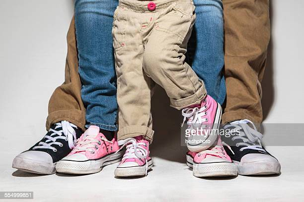 Feet and legs of family with toddler daughter