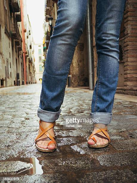 feet and legs of girl in sandals and jeans - wet jeans stock photos and pictures
