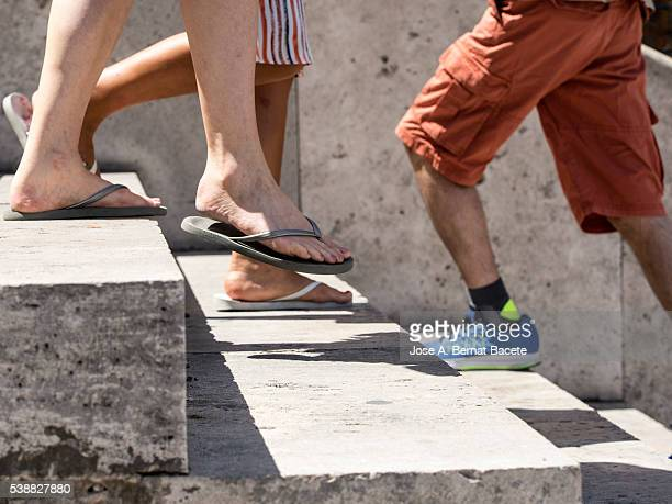 Feet and legs of young persons in summer raising and lowering steps
