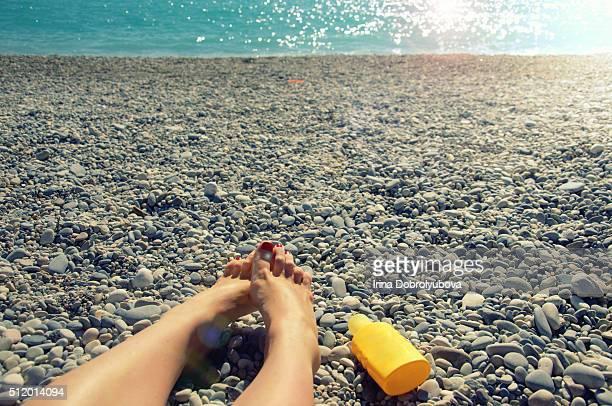 feet and sunscreen bottle