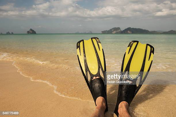 Feet in diving fins on beach