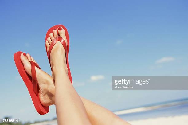 Feet in flip flops on beach