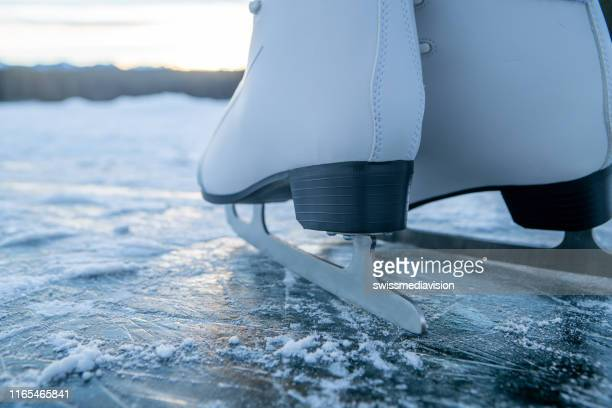 feet in ice skates on frozen lake at sunset - skating stock pictures, royalty-free photos & images