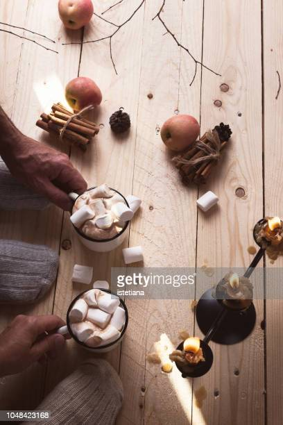 feet in wool socks. mature couple relaxing with mugs of hot chocolate and marshmallow - hygge stock-fotos und bilder