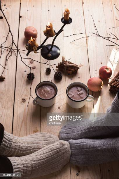 feet in wool socks. mature couple relaxing with mugs of hot chocolate - hygge stock pictures, royalty-free photos & images