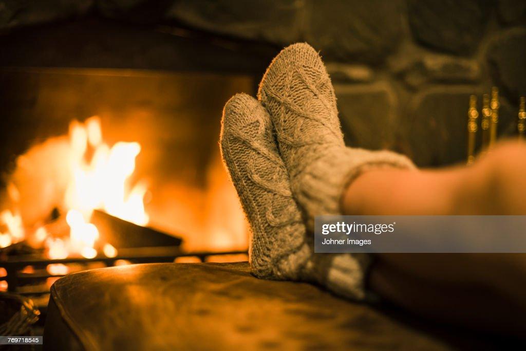 Feet in wool socks near fireplace : Stock Photo