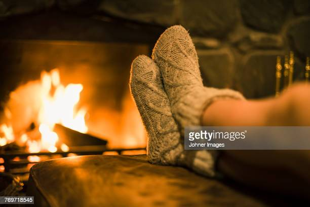 Feet in wool socks near fireplace