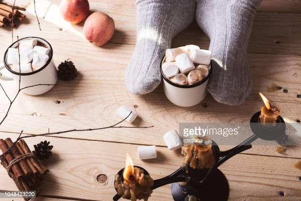 feet in wool socks on wooden floor. mature man relaxing with mug of hot chocolate - hygge stock pictures, royalty-free photos & images