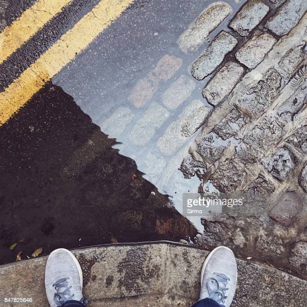 feet next to a london puddle - shoreditch stock photos and pictures