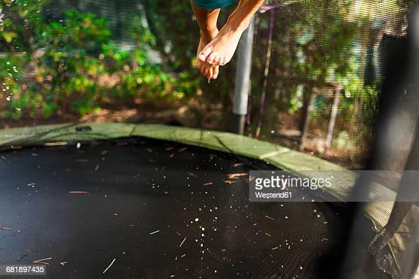 Feet of a boy jumping on trampoline
