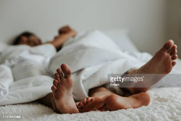 Feet of a couple in a bed - Stock image