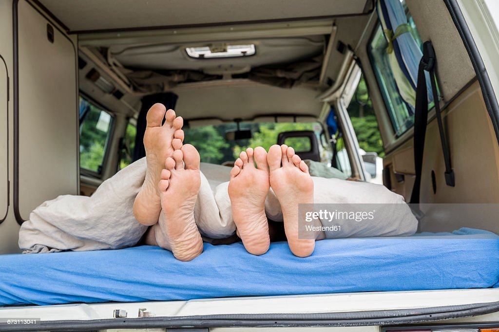 Feet of a couple lying on mattress in van : Stock Photo