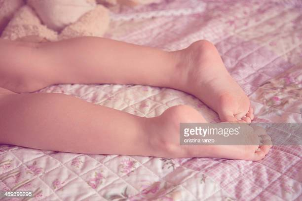 Feet of a little girl lying on bed in pastel color