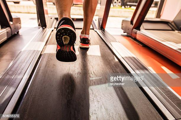 Feet of a runner on treadmill in a gym.