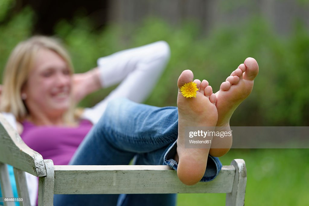 Feet of a woman with dandelion between toes : Stock Photo