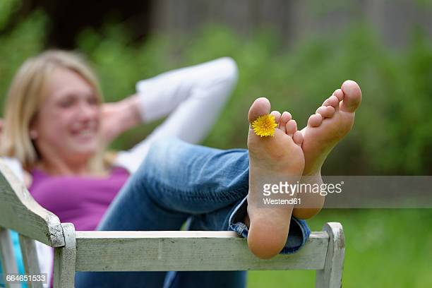 feet of a woman with dandelion between toes - female feet soles stock photos and pictures