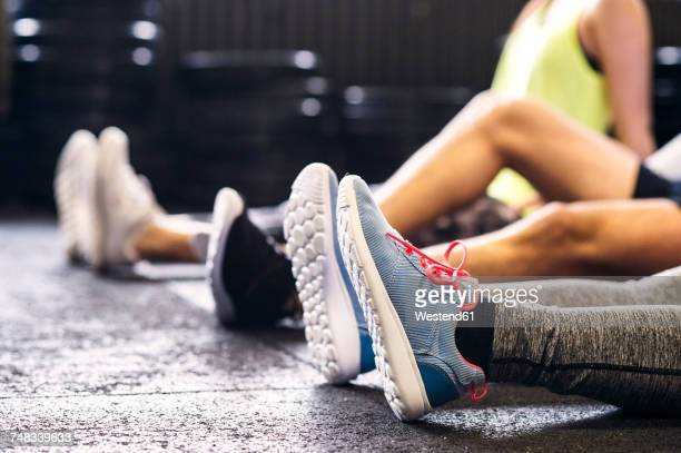feet of athletes sitting on floor in gym - teen feet stock photos and pictures