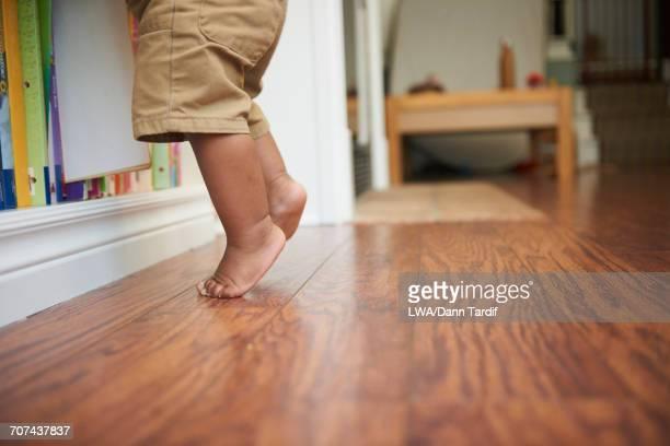 Feet of Black baby boy standing tiptoe