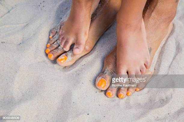 Feet of black mother and daughter standing on beach
