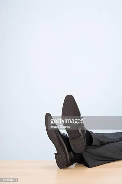Feet of businessman on desk
