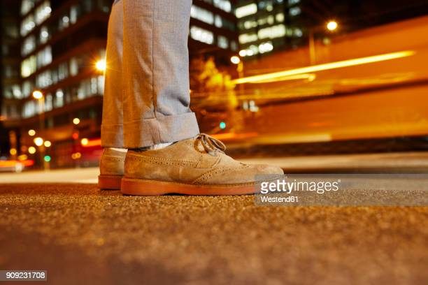 Feet of businessman standing at roadside in the city at night, close-up