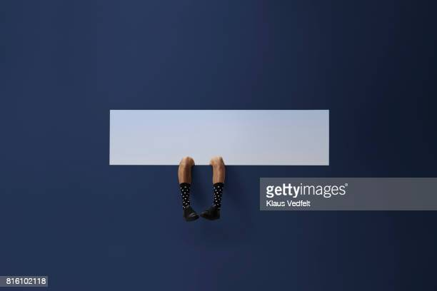 feet of businessman, sticking out rectangular opening in coloured wall - men in white socks fotografías e imágenes de stock