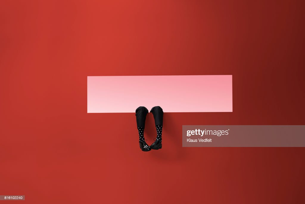 Feet of businessman, sticking out rectangular opening in coloured wall : Stock Photo