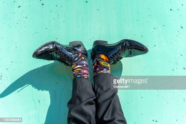 feet of businessman wearing colorful socks against green wall - multi colored shoe stock pictures, royalty-free photos & images
