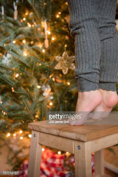 Feet of Caucasian girl standing on stool decorating Christmas tree