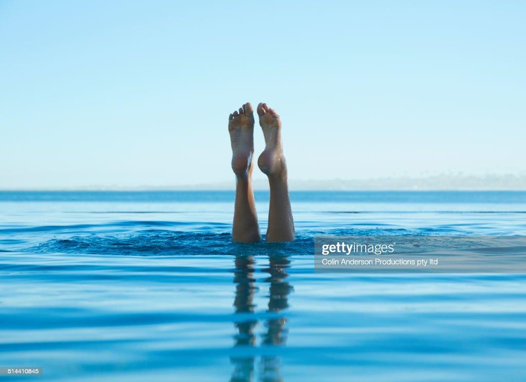 Feet of caucasian girl swimming in tropical ocean : Stock Photo
