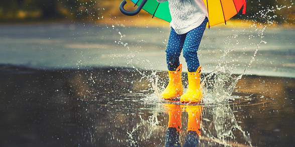 Feet of  child in yellow rubber boots jumping over  puddle in rain 835991656