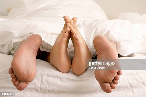 Feet of couple hanging out of bed