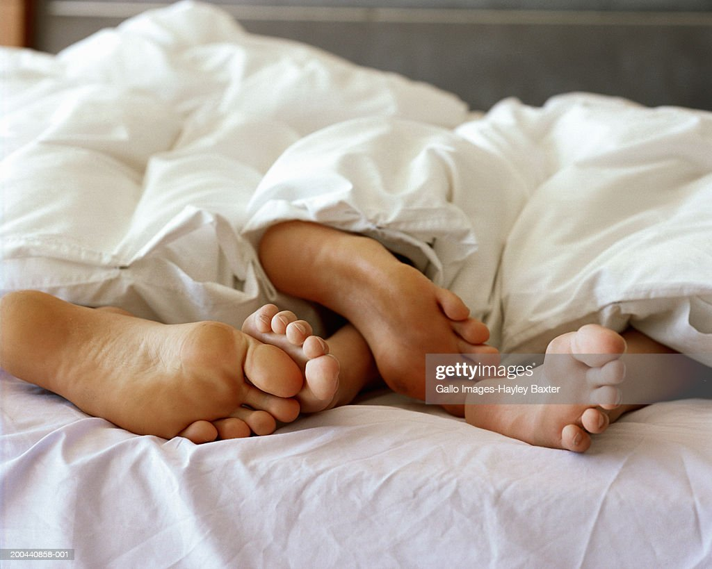 Feet of couple sticking out from under duvet, close up : Stock Photo