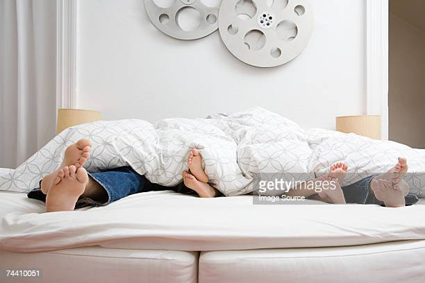 feet of family in bed - double bed stock pictures, royalty-free photos & images