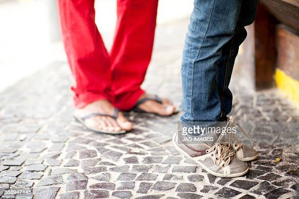 Feet of father and tiptoeing son at beach bar, Ipanema beach, Rio De Janeiro, Brazil