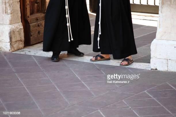 Feet of Franciscan monks in black habit