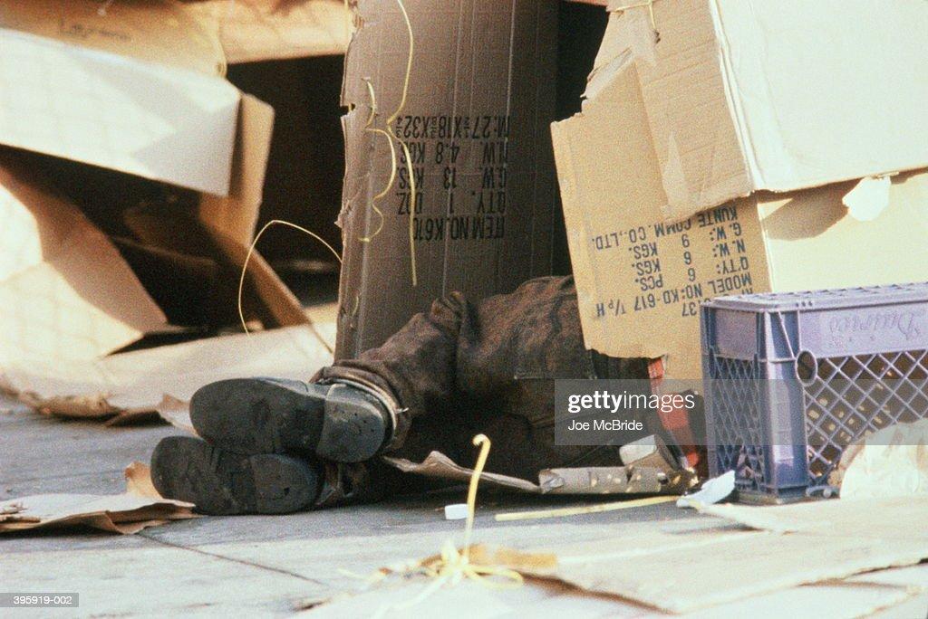 Feet of homeless person sleeping in cardboard box : Stock Photo