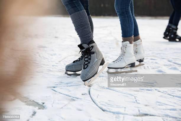 feet of ice skating people on frozen lake - スケート靴 ストックフォトと画像