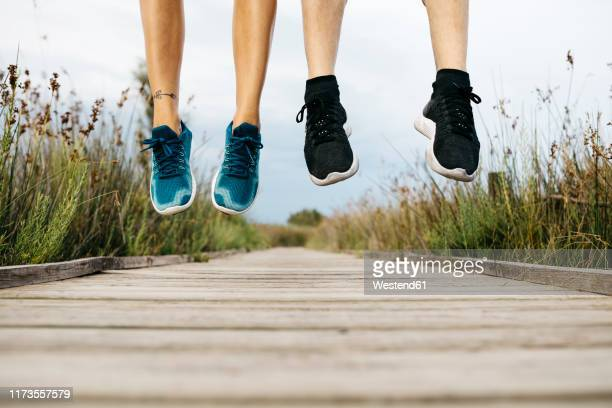 feet of joggers jumping on a wooden walkway - low section stock pictures, royalty-free photos & images