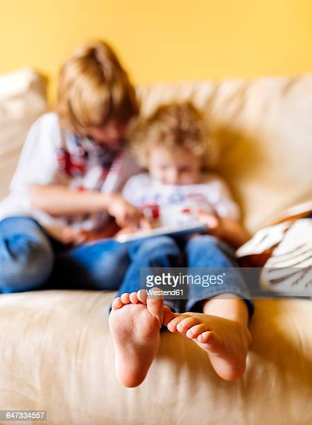 Feet of little boy sitting on couch with his brother, close-up