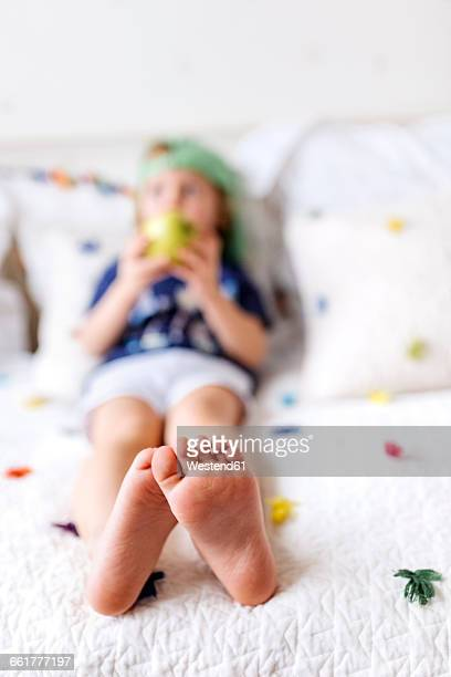 Feet of little boy sitting on the couch eating an apple