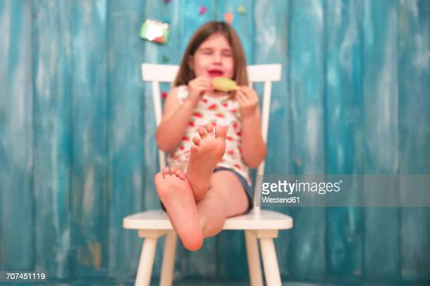 Feet of little girl sitting on chair eating lemon ice lolly