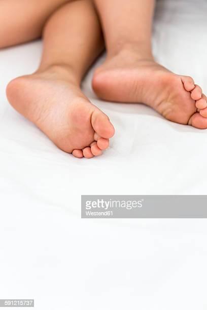 Feet of little girl sleeping in bed
